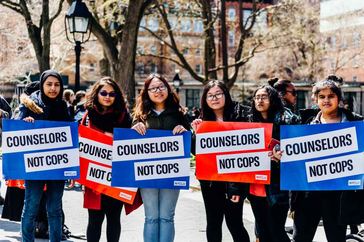 """Students holding posters that say """"Counselors Not Cops"""