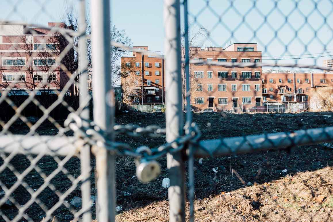 Photo of a locked gate in front of an empty lot on the Broadway Triangle site