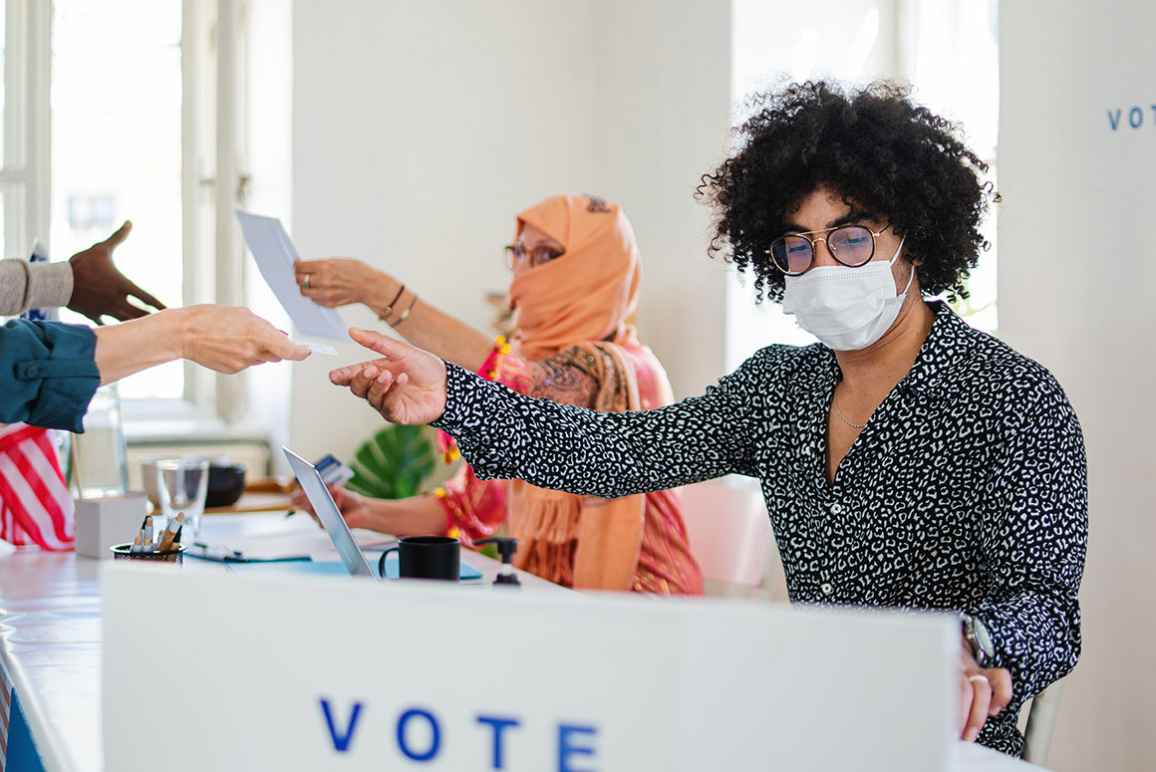 Poll worker wearing a face mask.