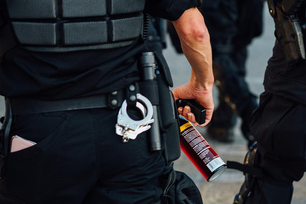 Police holding pepper spray. Photo by Adam Cohn.